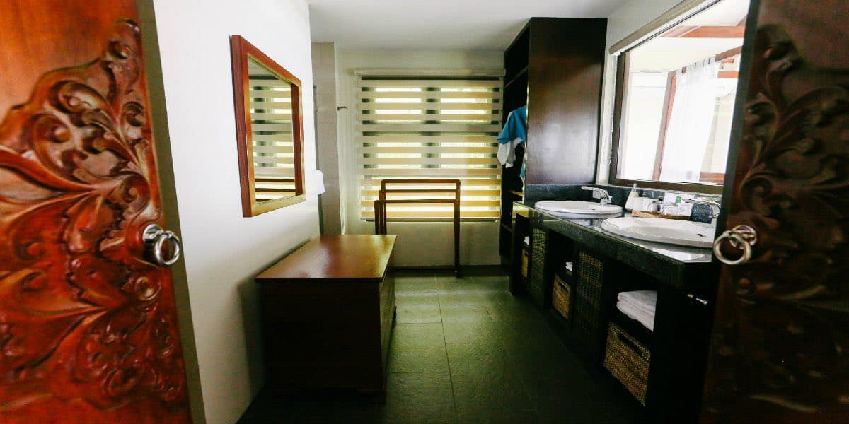 Bedroom 1: En-suite, dual sink with an internal picture window, rain shower, and separate lavatory.